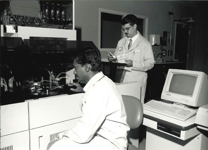 Two employees in the early 1980s using an automated analyzer, a lab instrument used to measure specimen sample characteristics.