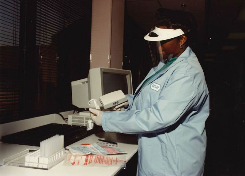 An employee in the early 1990s using an early barcode reader used to accession drug testing specimens.